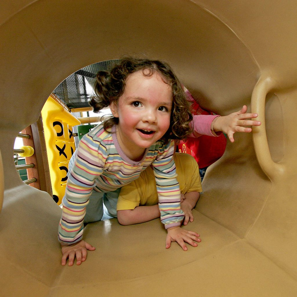 Small child climbs through Soft Play tunnel