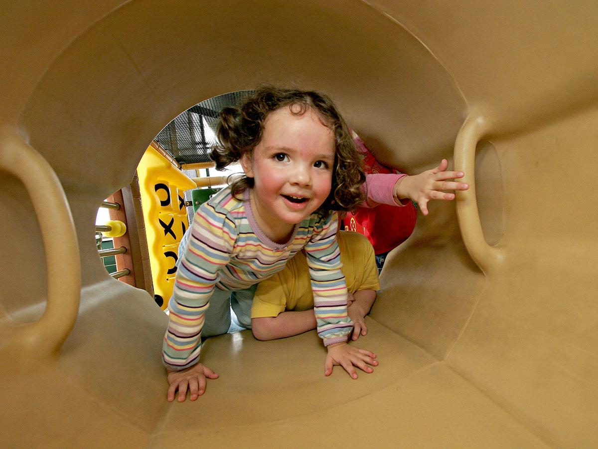 Small child climbs through Soft Play tunnel