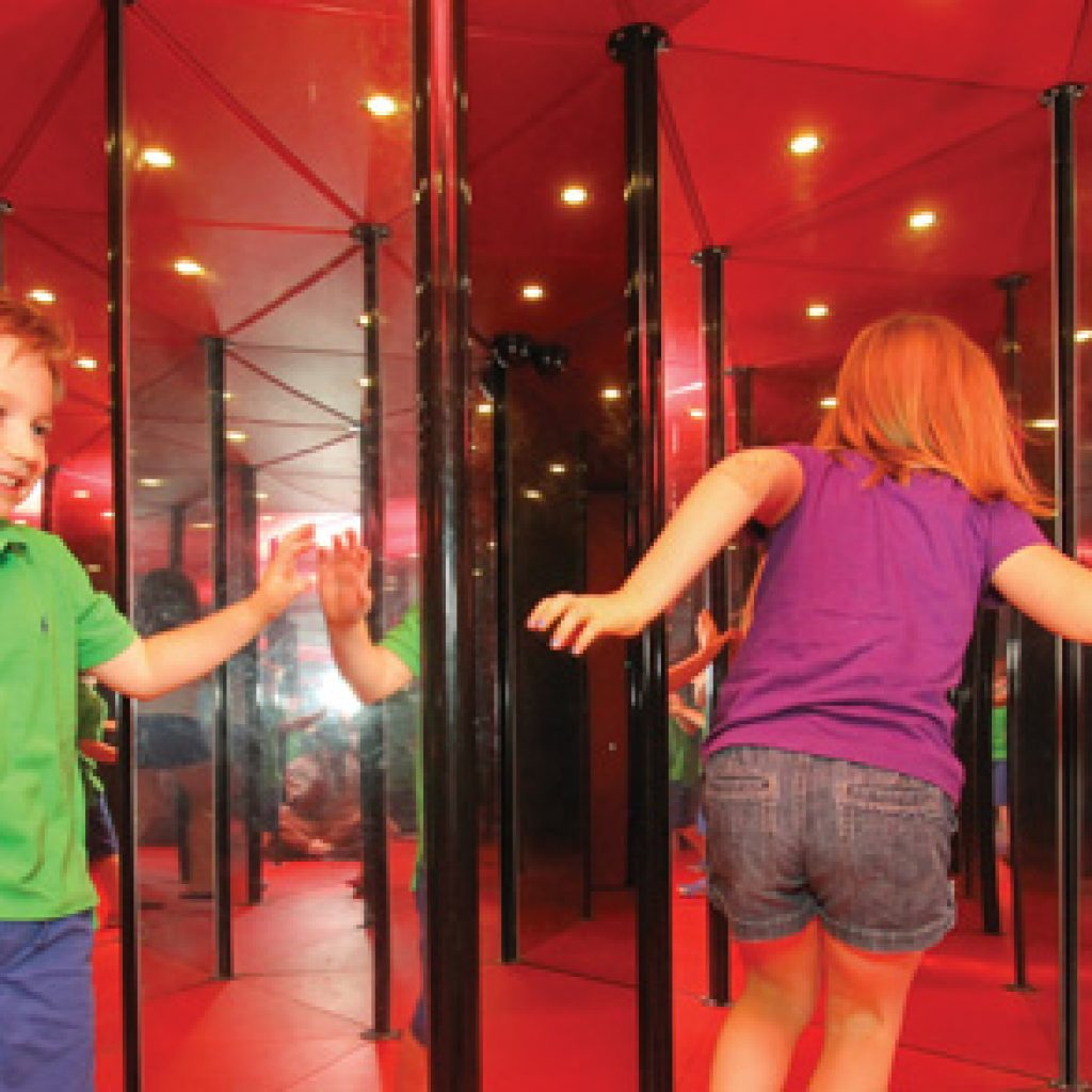 Young girl and boy playing in maze of mirrors