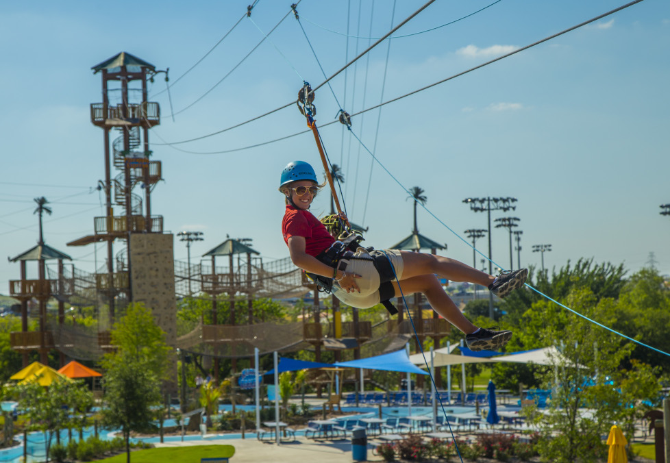 Woman riding a zip line on the High Rope Adventure Course