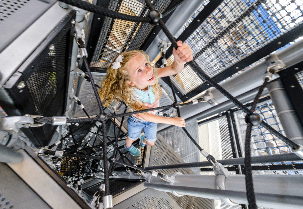 Girl climbing the rope maze inside the Adventure Course Tower