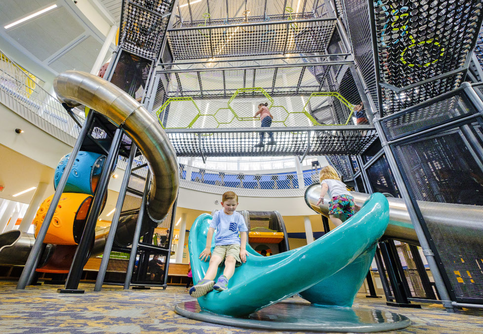 Children playing on the Adventure Course play structure and net skyway