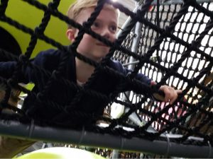 Boy balancing on net in hive challenge course